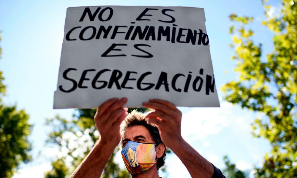 "A protester holds a sign reading ""It is not confinement but segregation"" during a demonstration against the restrictions imposed by the regional government to fight the coronavirus spread at the Vallecas district in Madrid, on September 27, 2020."