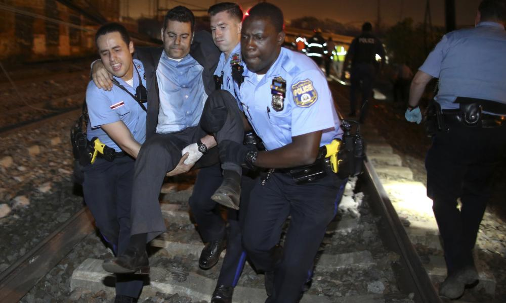 Emergency personnel help a passenger at the scene of the Amtrak train crash in Philadelphia on Tuesday.