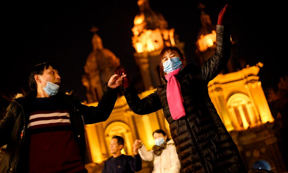 People wearing face masks dance in front of the St. Joseph's Church in Beijing on 21 December 2020.