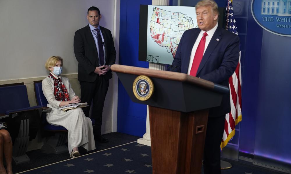 White House coronavirus response coordinator Dr. Deborah Birx, left, listens as President Donald Trump speaks during a news conference in Washington.