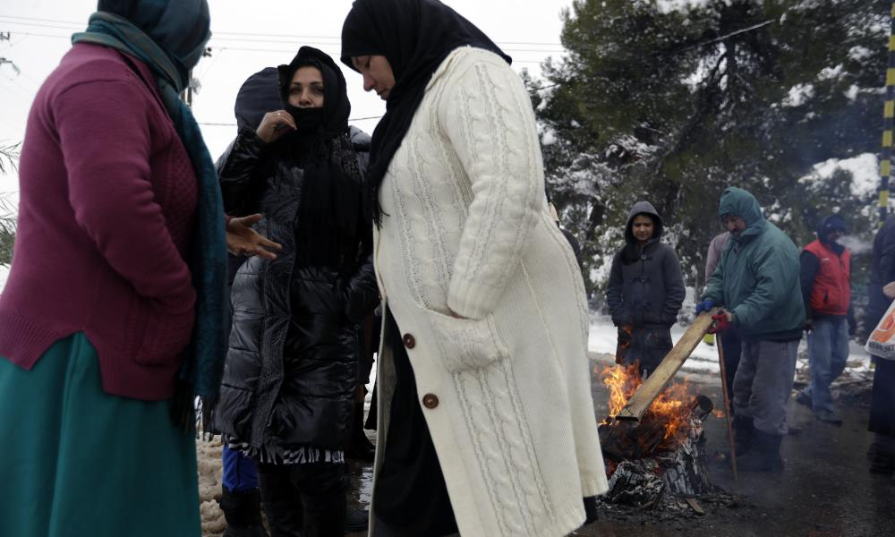 Afghans try to warm themselves around a fire during a protest demanding better living conditions outside a refugee camp in Malakasa,  north of Athens.