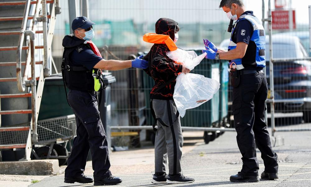 A migrant rescued from the Channel by UK Border Force arrives at Dover harbour.