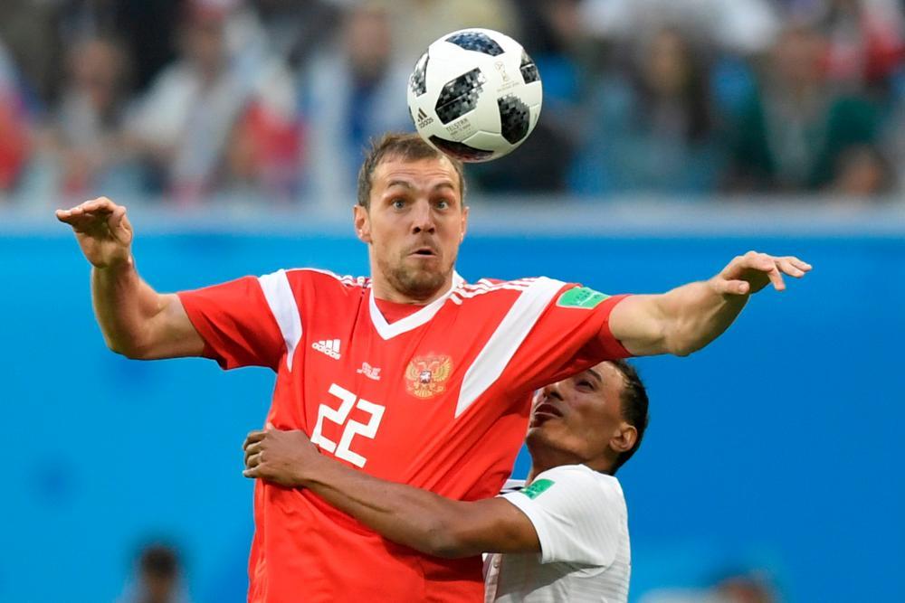 Russia's forward Artem Dzyuba tries to bring down the ball.