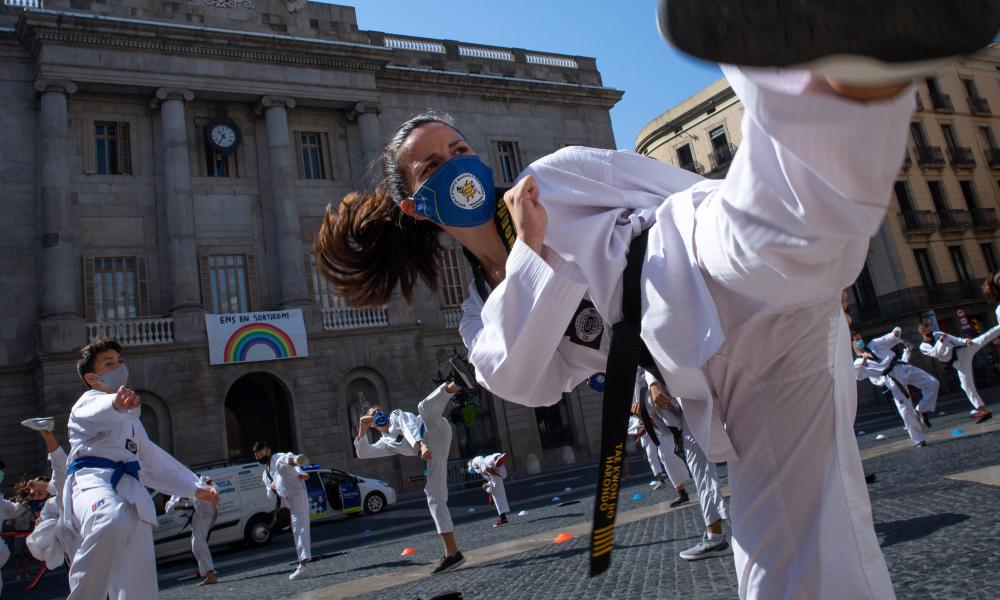 Dozens of people practice martial arts in front of the regional government headquarters in Barcelona, Spain, as a protest against the closure of gyms and martial arts centres in the region due to coronavirus