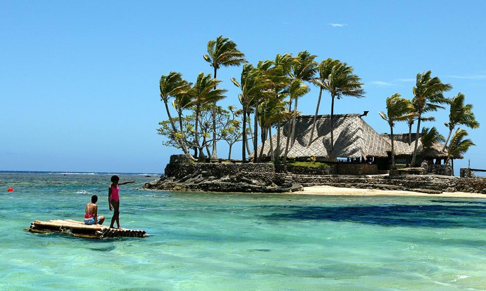 Children float on a bamboo pontoon by Wicked Walu Island on the Coral Coast of Fiji