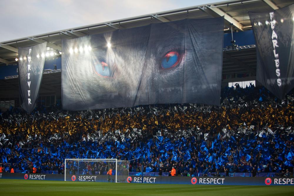 The Leicester City fans wave blue, silver and gold flags before the start.