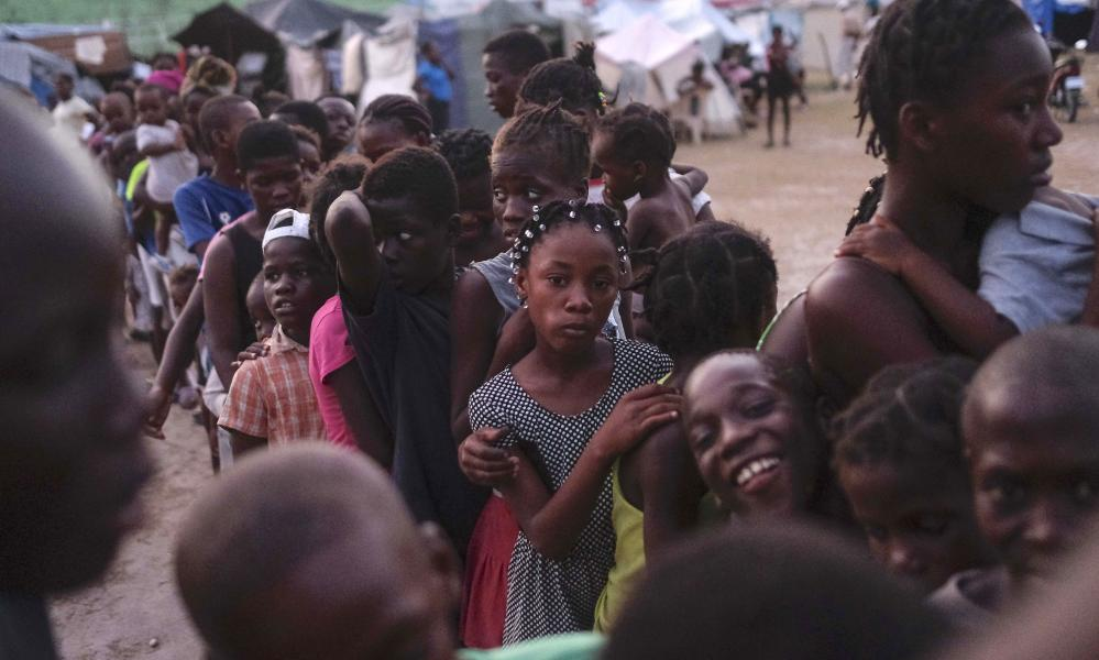 Children line up to receive food aid at the refugee camp in Les Cayes, Haiti