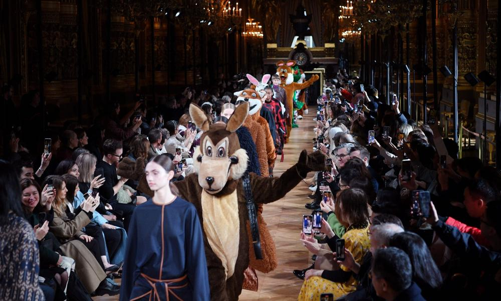 Performers in animal costumes join models on the catwalk