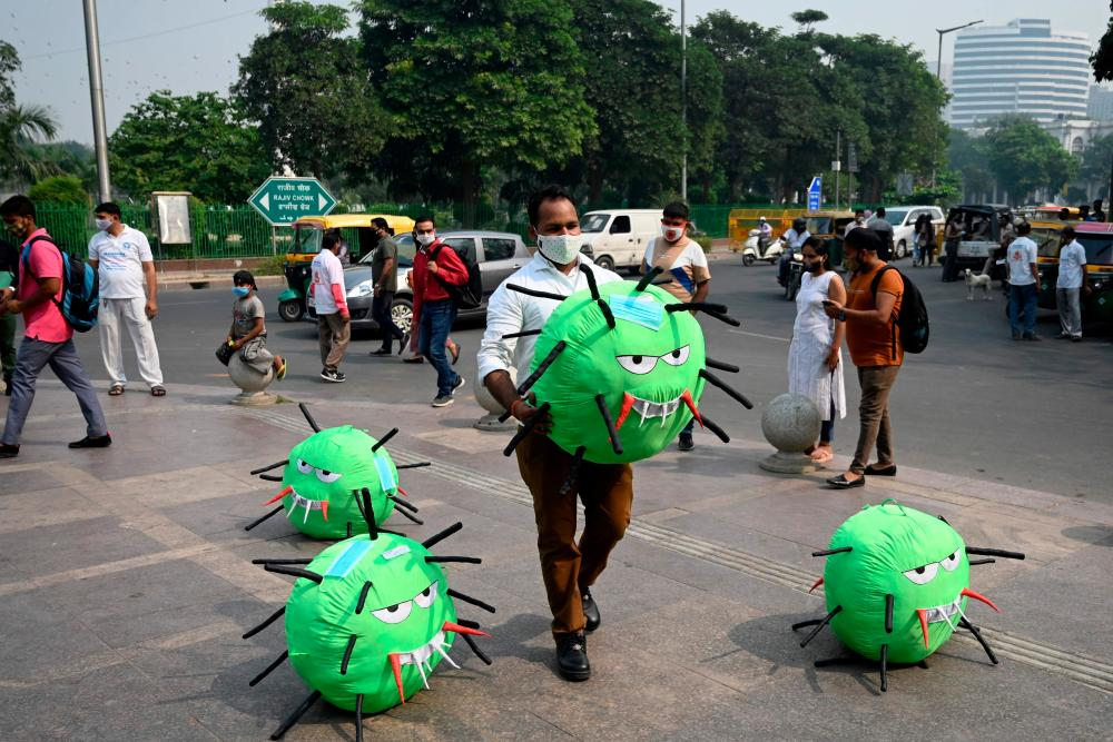 An officer from the New Delhi district magistrate office holds a Covid-19 coronavirus-themed mascot in a market area during an awareness campaign.