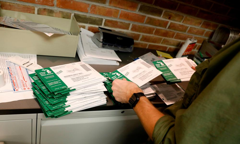 In West Bloomfield, Michigan, an employee of the West Bloomfield Township Clerks office checks to see if the absentee ballots are at the right clerks office and has a signature on October 31, 2020. More than a third of registered voters in Michigan, 2.6 million people, have already cast a ballot, according to Michigan secretary of state Jocelyn Benson.