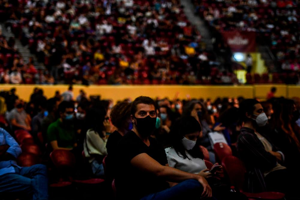 People wearing face masks attend a concert in Lisbon.