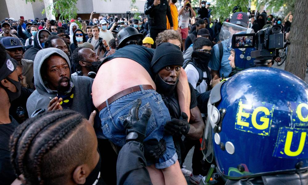 A group of men carry an injured man away after he was allegedly attacked by some of the crowd of protesters as police try to intervene on the Southbank near Waterloo station on June 13, 2020 in London, United Kingdom.