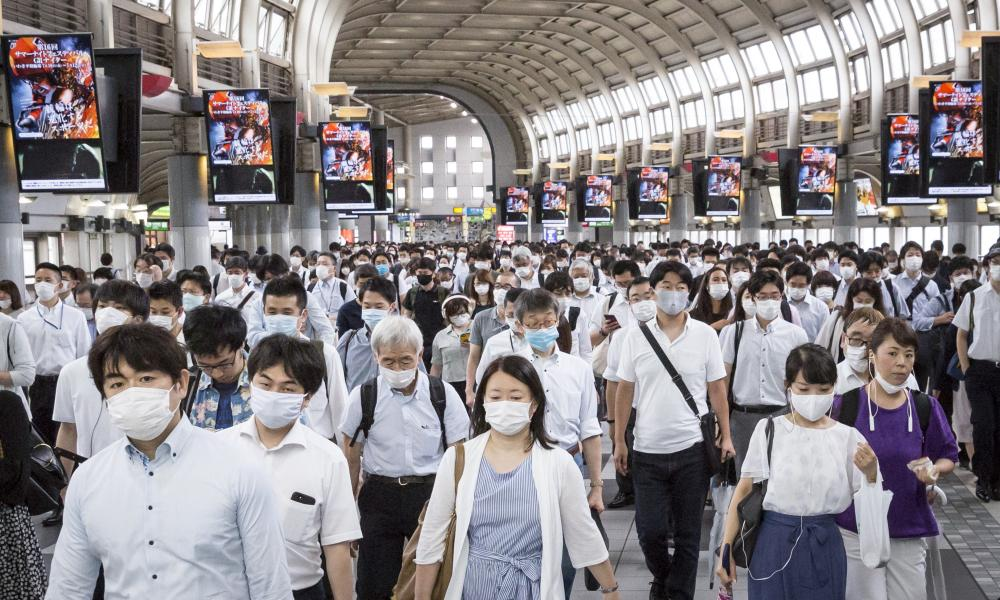 Commuters wearing face masks pass through Shinagawa train station in Tokyo on July 10.