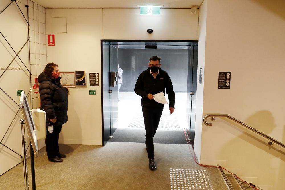 Victorian premier Daniel Andrews walks into the daily briefing on Sunday.