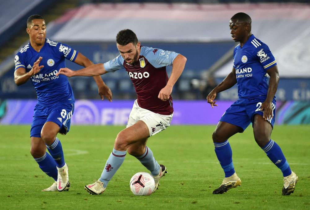 John McGinn of Aston Villa is challenged by Youri Tielemans and Nampalys Mendy of Leicester City.