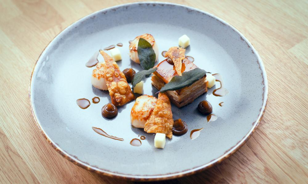 Dish of pork belly, scallops, crispy sage and burnt apple purée at Abbots Court, Winterborne Kingston, Dorset, UK.