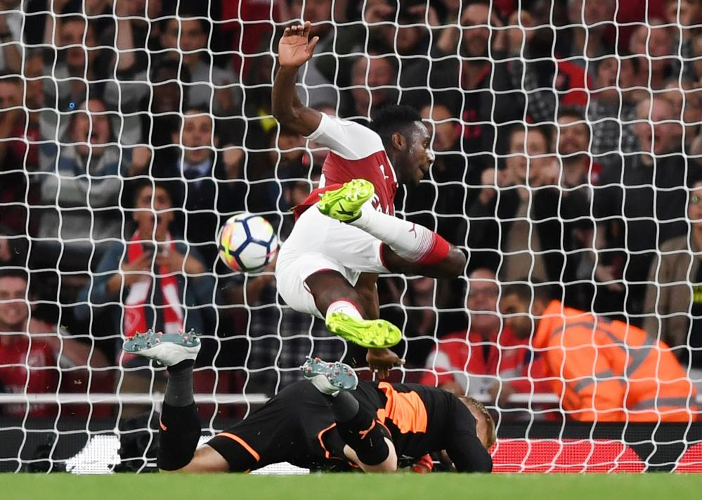 Danny Welbeck collides with Kasper Schmeichel as he scores Arsenal's second goal.