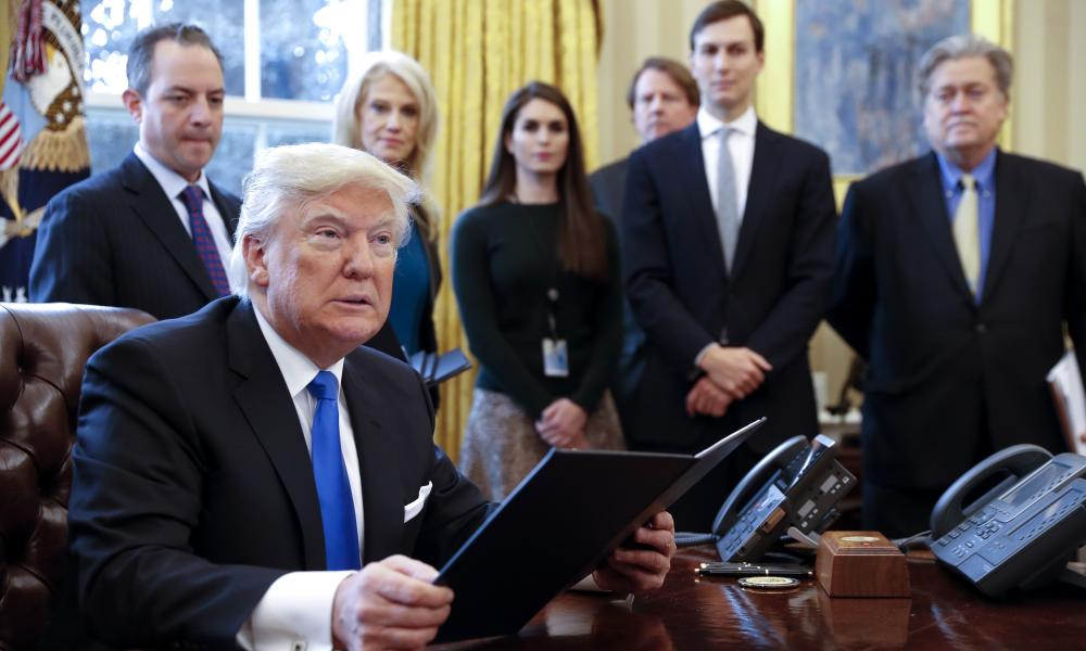 Trump with staff including Kellyanne Conway (second left), Jared Kushner (second right) and Steve Bannon (far right), 24 January 2017.