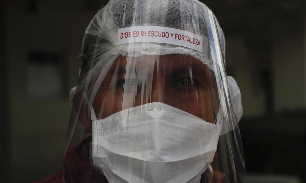 """A health worker in full protective gear and with a face shield with text that reads in Spanish """"God is my shield and my strength,"""" attends an official act by local authorities as they hand over hospital beds to the Del Norte Hospital, which is treating COVID-19 patients exclusively, in El Alto, Bolivia."""