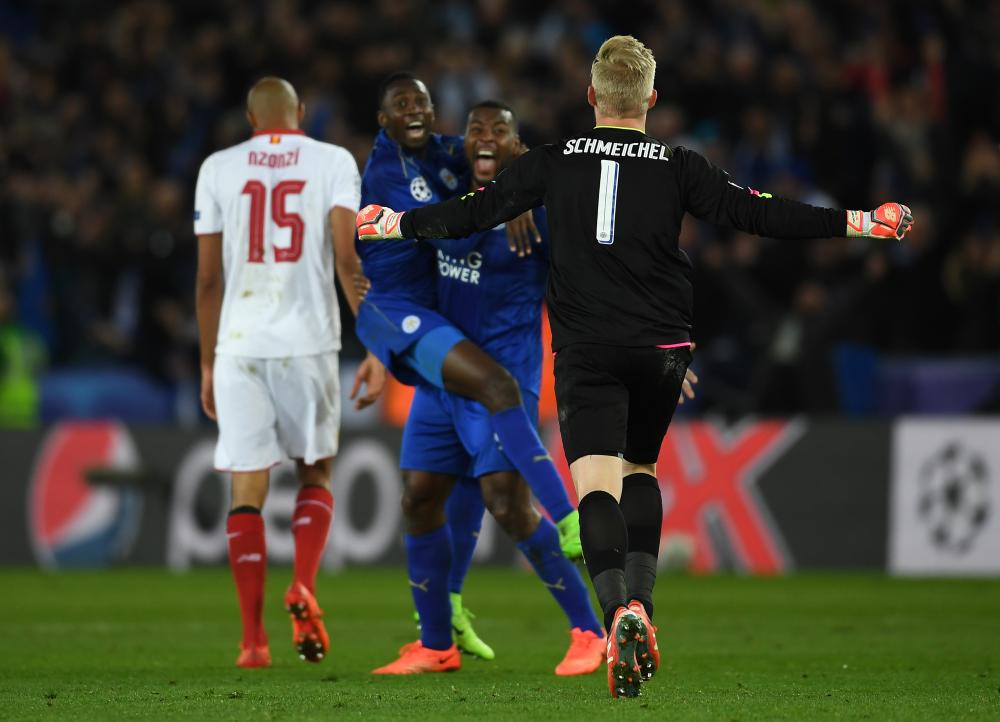 Kasper Schmeichel runs to celebrate with team-mates Wilfred Ndidi and Wes Morgan as the final whistle blows.