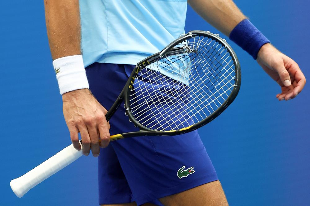 Djokovic holds his broken racket.