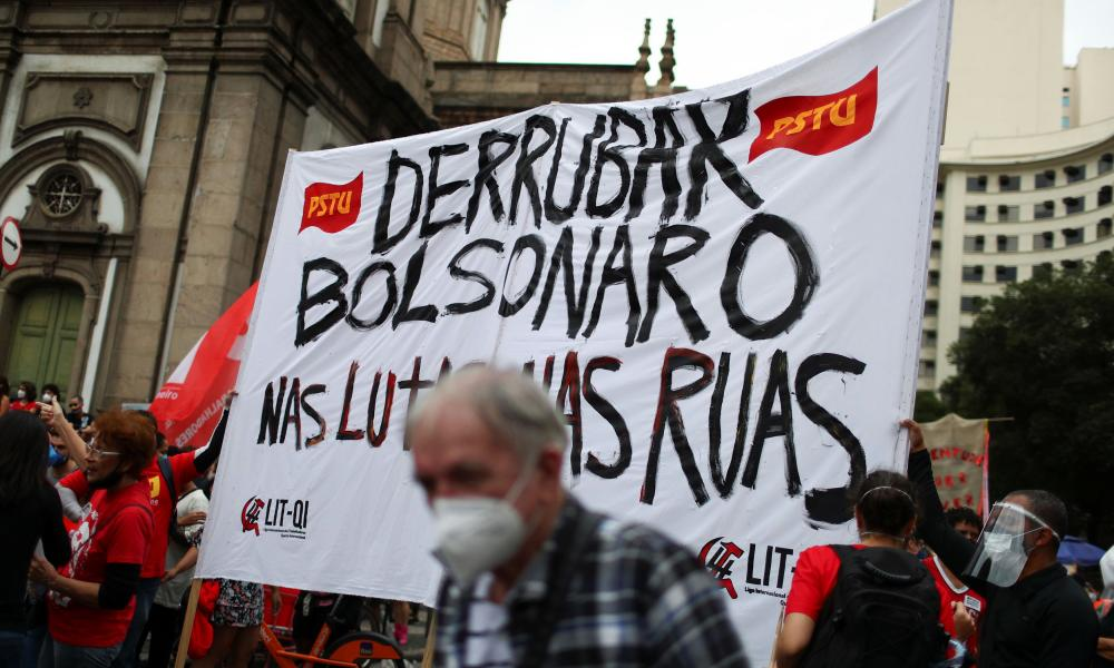 """People hold a banner during a demonstration against Brazil's President Jair Bolsonaro's handling of the pandemic and to impeach him, in Rio de Janeiro, Brazil,. The banner reads: """"Take Bolsonaro down in fights and on the streets""""."""