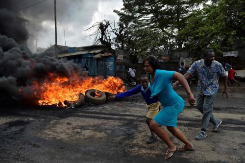 A woman leads a school pupil away from teargas