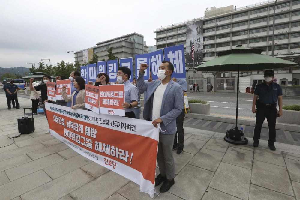 """Protesters stage a rally to oppose a planned visit by U.S. Deputy Secretary of State Stephen Biegun near the US Embassy in Seoul. The letters read """"We demand the dissolution of the US and South Korea working group."""""""
