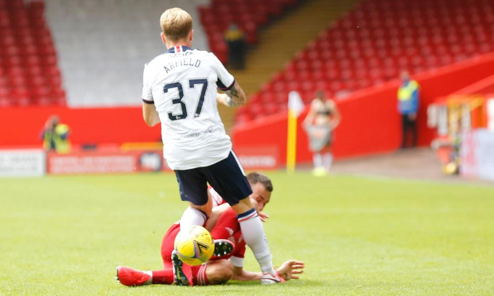 Aberdeen defender Andrew Considine slides in on Rangers' Scott Arfield and is shown a red card.