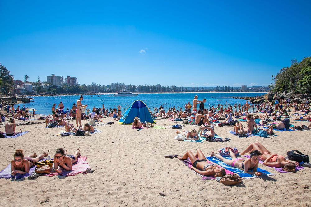 People relaxing on sandy Shelly beach at Manly in Sydney, Australia