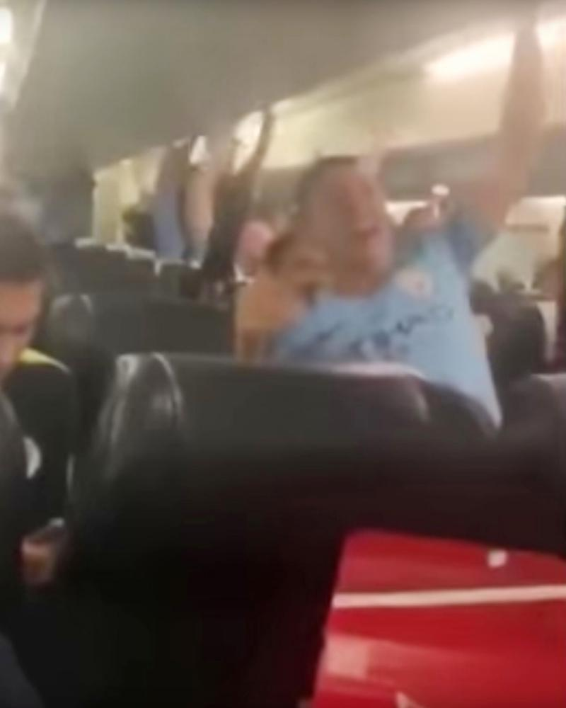 An image from footage showing Manchester City staff singing their supporters' version of the Allez, Allez' Allez song on a flight back from Brighton Sunday