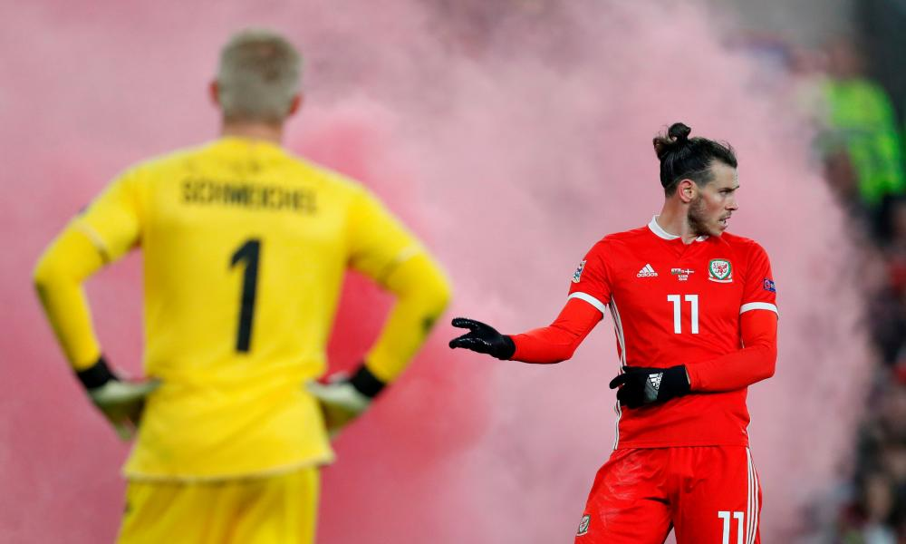 Gareth Bale and Kasper Schmeichel wait for play to restart after a flare was thrown onto the pitch by home fans.