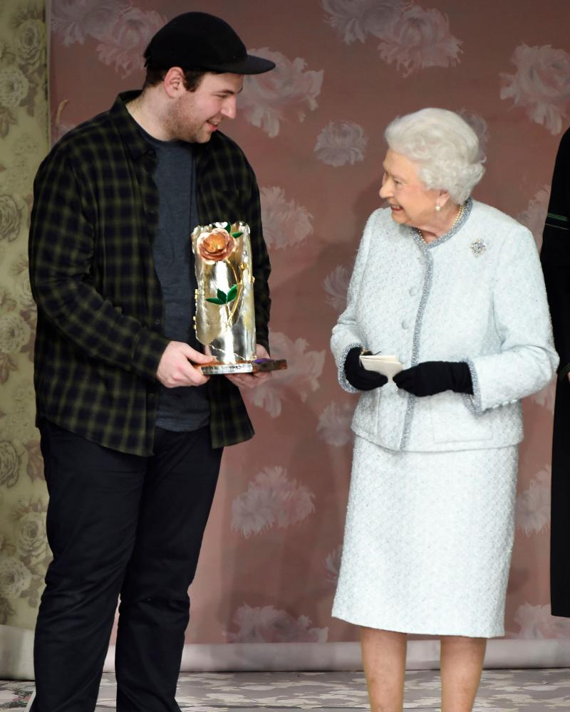 Richard Quinn receives his award from the Queen.