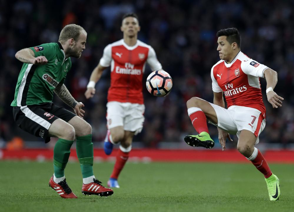 Arsenal's Alexis Sanchez, right, attempts to get past Lincoln City's Adam Marriott.