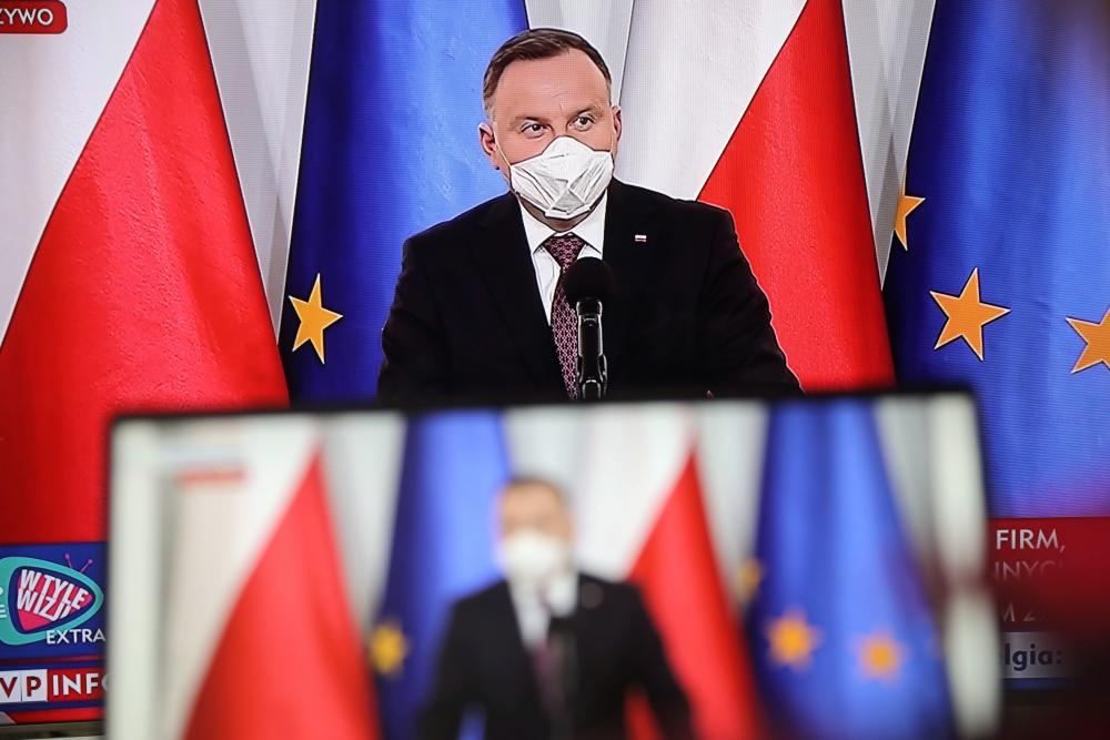 Polish president Andrzej Duda speaking at a press conference, watched in an apartment in Warsaw