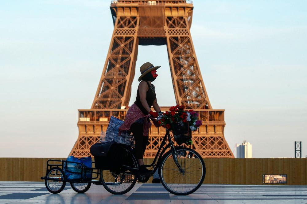 A woman rides her bicycle near the Eiffel tower at Trocadero square in Paris.