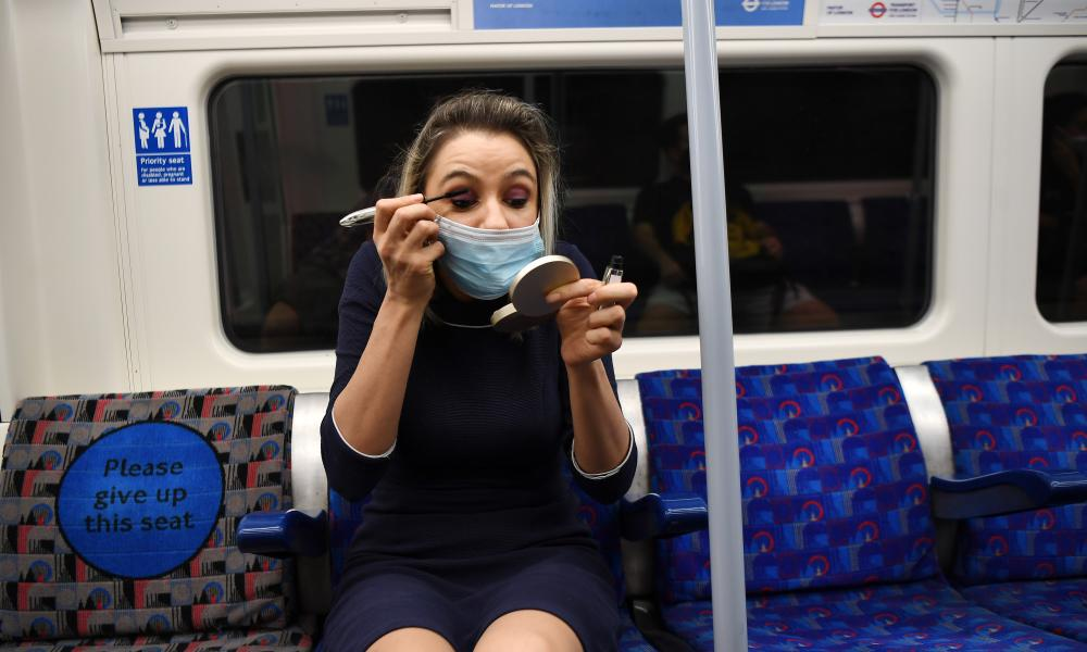 A commuter dons her make-up on an Underground train in central London.