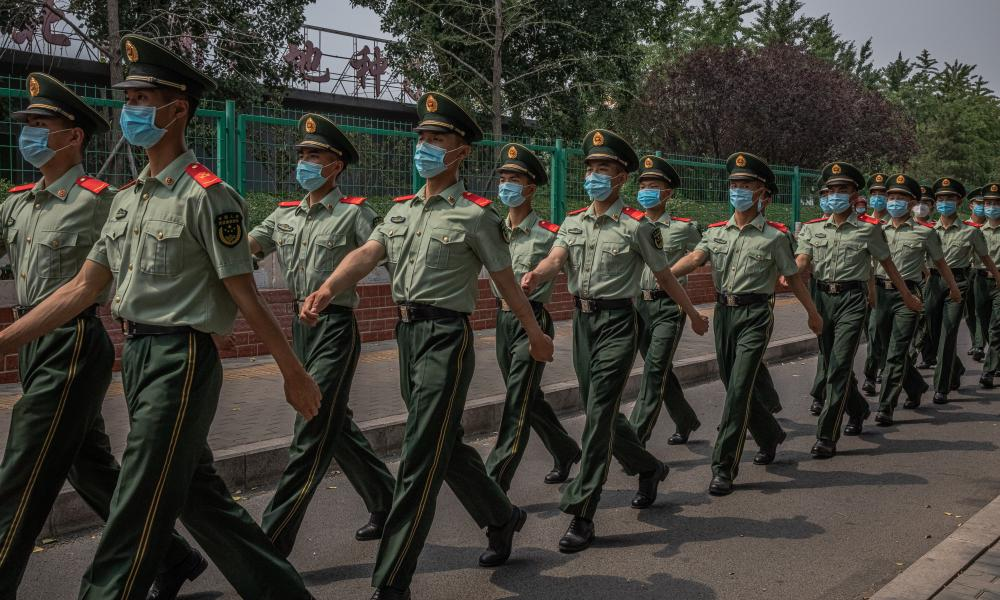 Chinese soldiers wearing face masks march next to the closed Xinfadi market building in Fengtai district, Beijing, China, on Saturday.