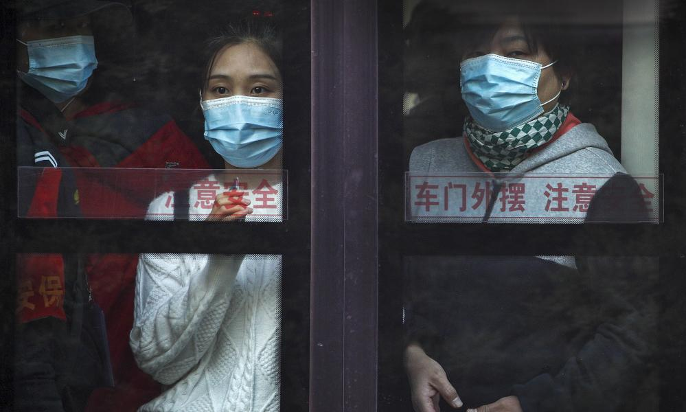 Commuters wearing face masks to help curb the spread of the coronavirus look out from a traveling bus during the morning rush hour in Beijing, Monday, 26 October, 2020.