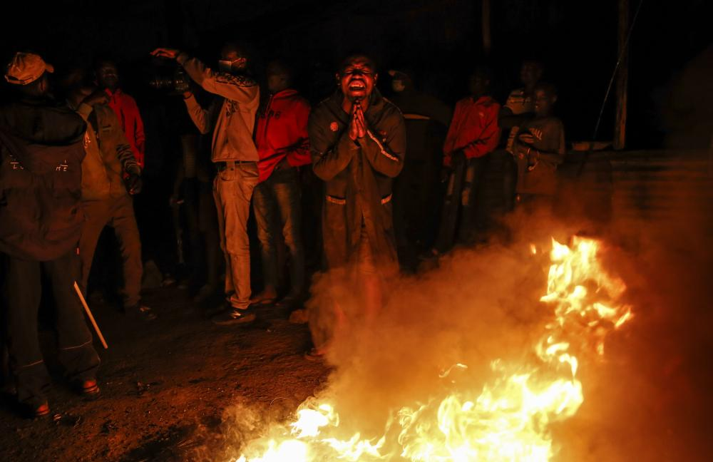 People burn tires as they protest over the killing of a homeless man by police enforcing a coronavirus curfew in Nairobi.
