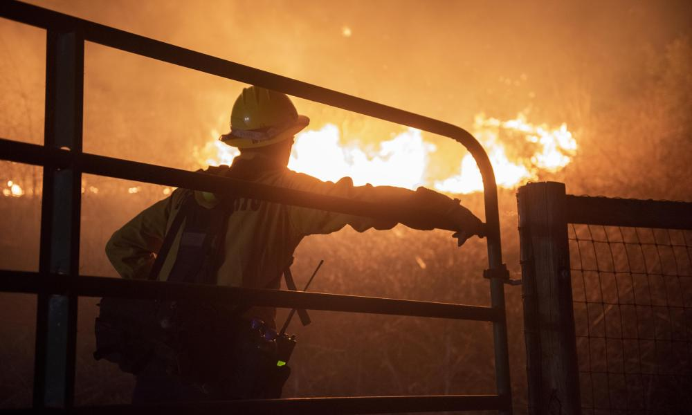 A firefighter from the Montecito fire department studies the Alisal fire as it drops into Refugio Canyon