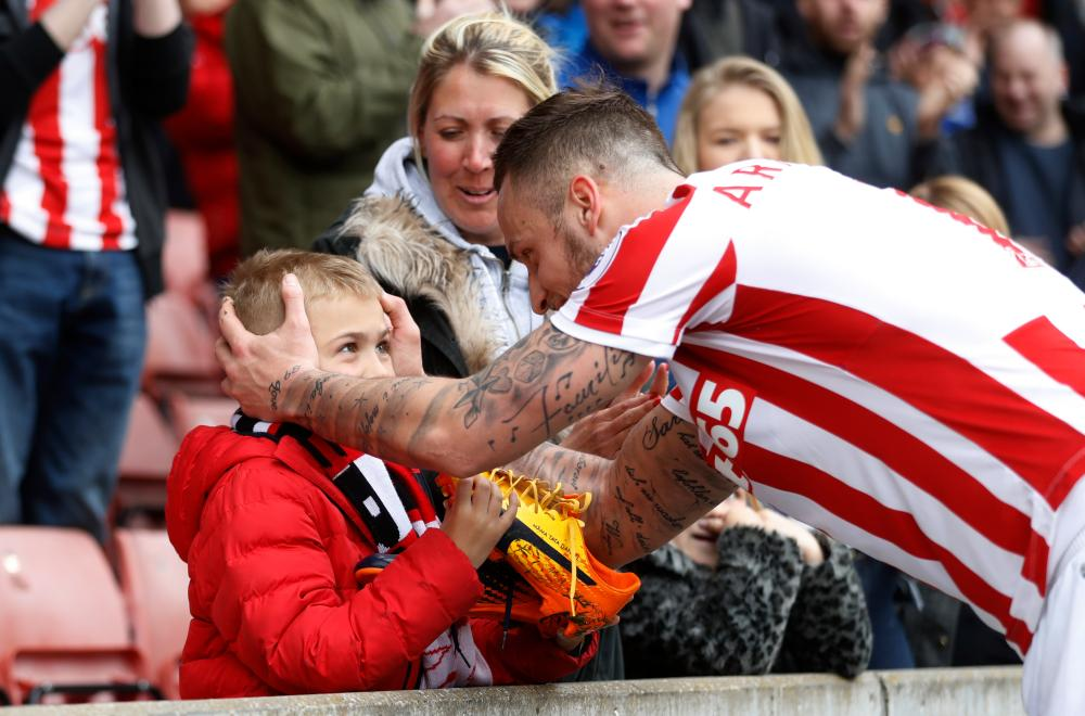Marko Arnautovic gives his boots to a young fan.
