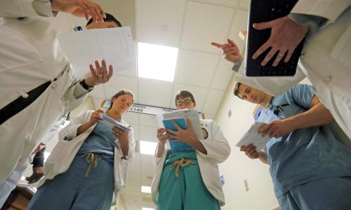 In a Friday, May 6, 2016 photo, Dr. Shane Prejean, left, goes over patient information with left to right, LSU medical students Felicia Venable, Kevin Francioni, medical residents Dr. Cameron Collier, and Dr. Wes Penn, during daily rounding at Our Lady of the Lake Regional Medical Center in Baton Rouge, La.Louisiana's deep, persistent budget troubles are endangering the future of medical training programs. Proposed cuts to hospitals could damage the stream of new doctors for a generation, in a state that has chronic shortages of health care workers and some of the worst health care outcomes in the nation.  (AP Photo/Gerald Herbert)