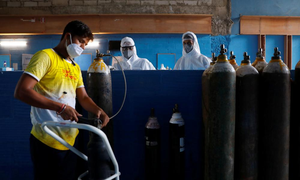 A worker refills an oxygen cylinder at a hospital in Noida, on the outskirts of New Delhi, India, on Tuesday.