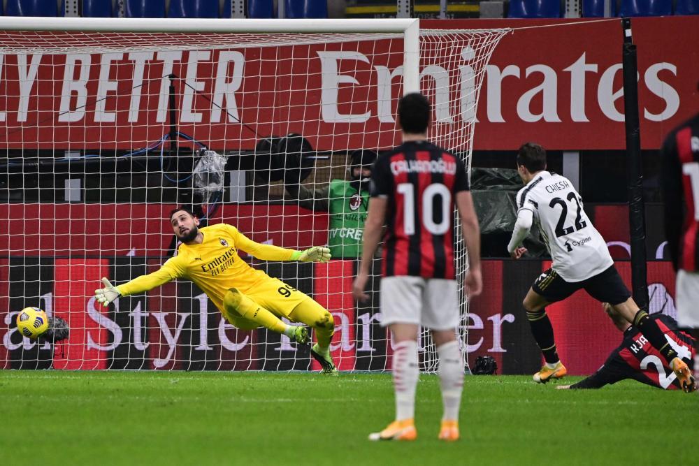 Juventus' Federico Chiesa (right) shoots past Milan's goalkeeper Gianluigi Donnarumma to open the scoring.