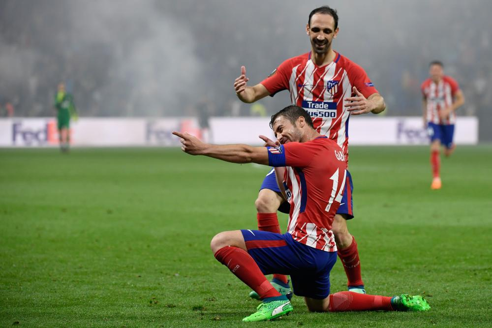 Atletico Madrid's midfielder Gabi celebrates past Atletico Madrid's Diego Godin after scoring