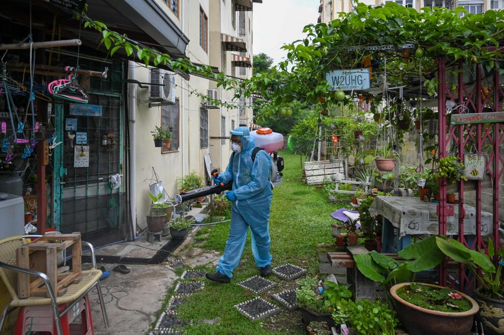A city council volunteer worker sprays disinfectant in the backyard of an apartment building in Kuala Lumpur.