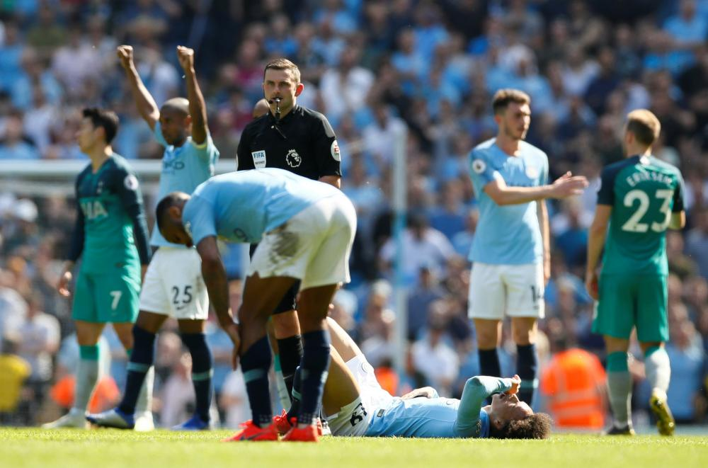 Manchester City's Leroy Sane, Fernandinho and team mates celebrate after the referee blows the final whistle.