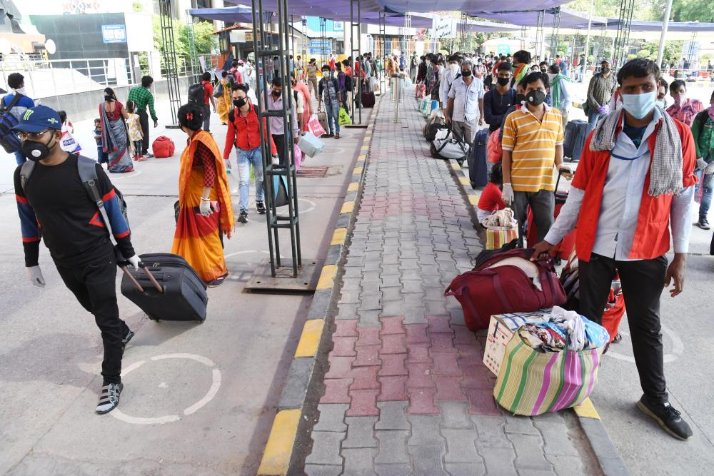 Passengers wait in queues as they arrive at the railway station in New Delhi.