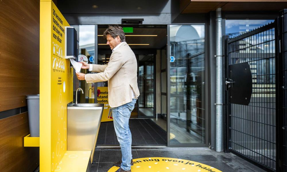 A man washes his hands at a McDonald's test location set up in a branch at GelreDome in Arnhem.